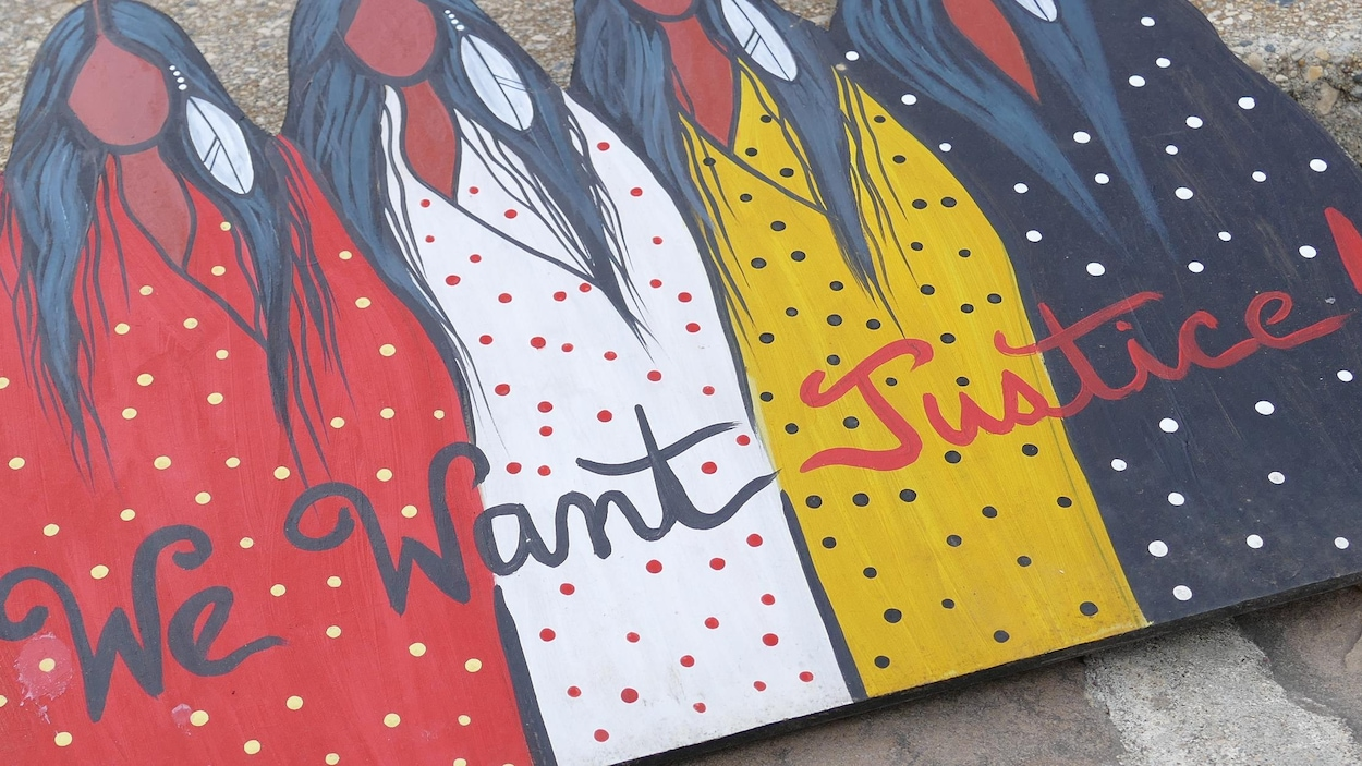 L'œuvre d'art est un tableau en bois avec quatre femmes autochtones peinturées. Le texte We want justice est écrit en italique.