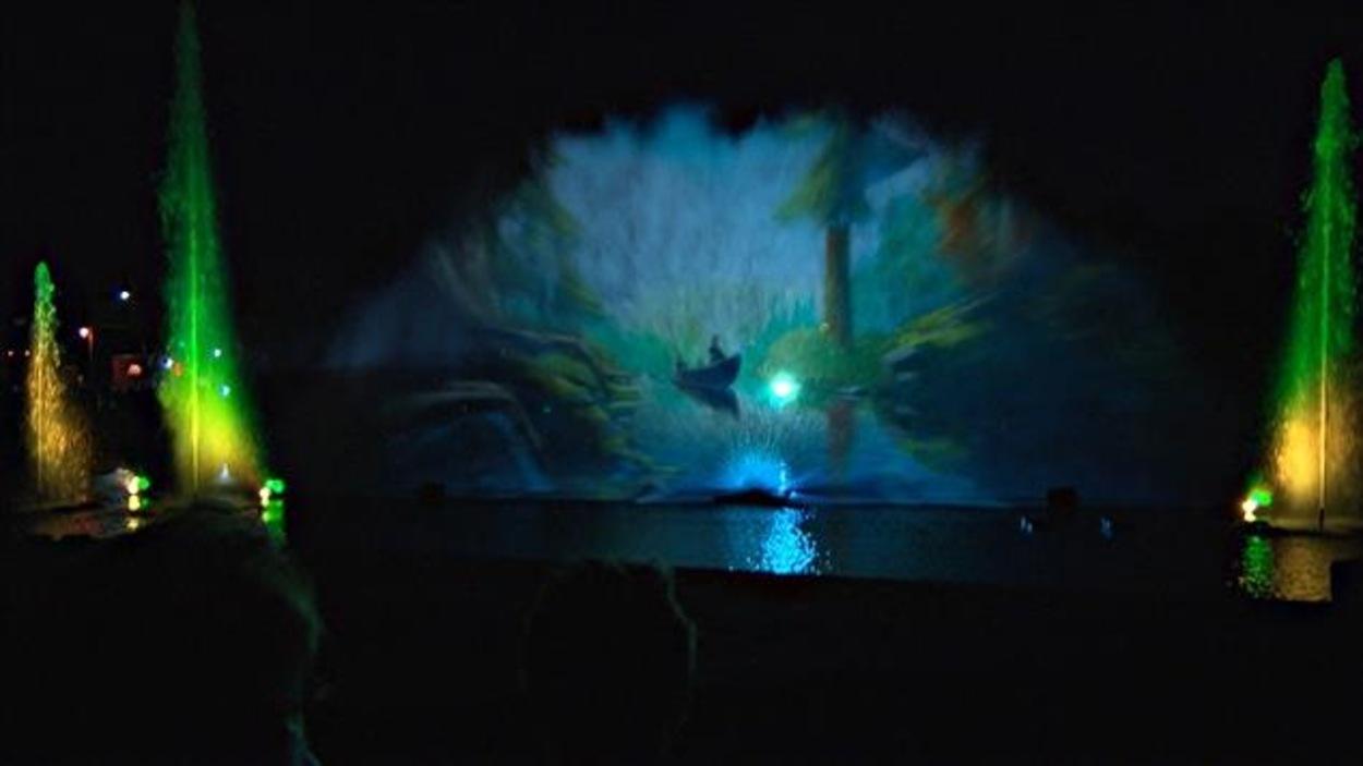 Une image apparaît au milieu de jets d'eau colorés.