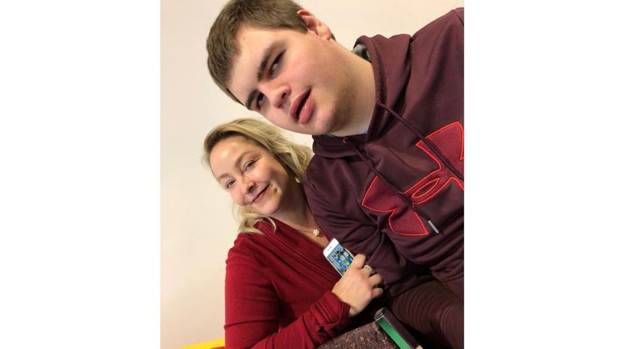 Sur la photo, une femme sourit en tenant son fils dans ses bras.