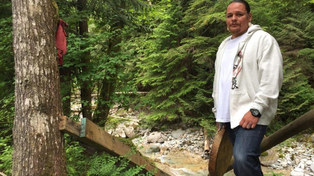 Un homme en jeans et chandail à capuchon devant une source naturelle, un tambour à la main.