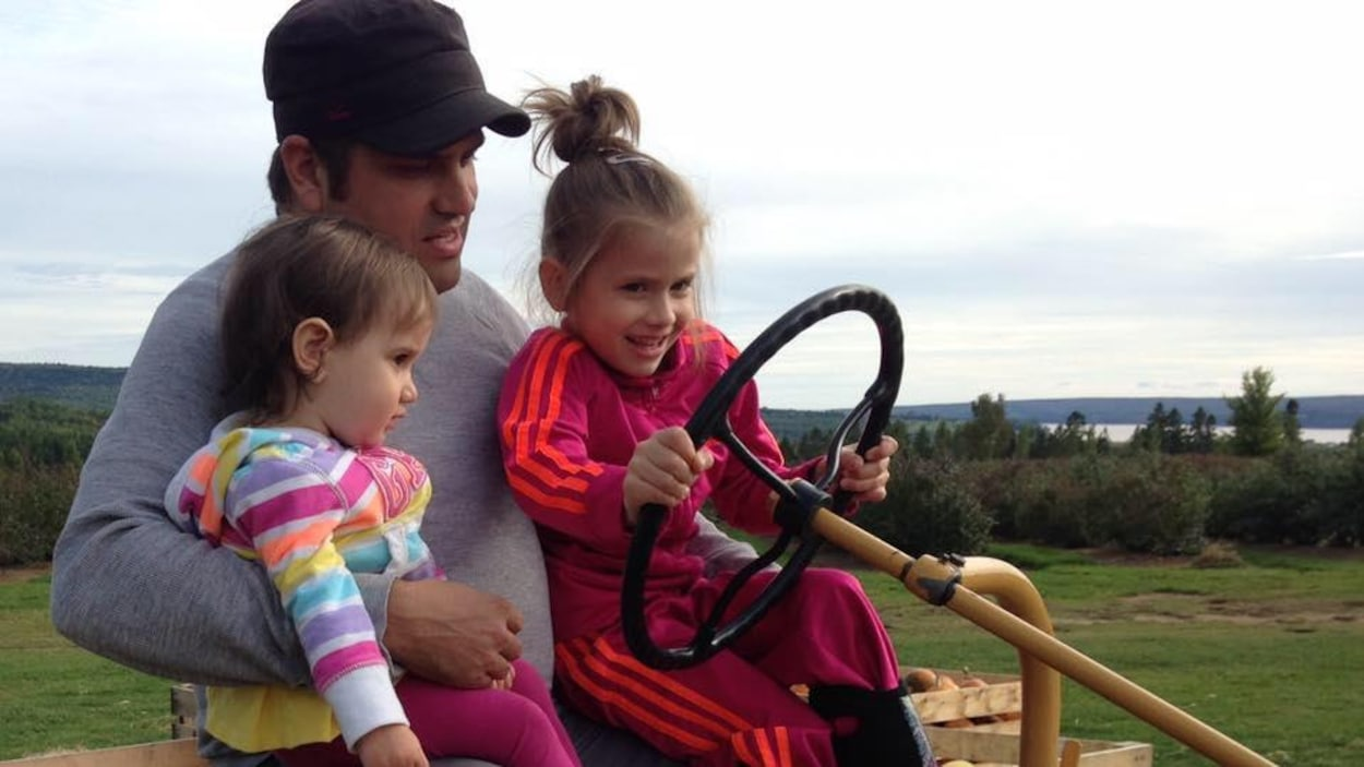 Mathieu Bernier et ses deux fillettes assis sur un tracteur de ferme