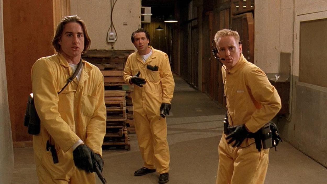 Trois hommes dans des combinaisons jaunes avec un pistolet et des ceintures d'outils.