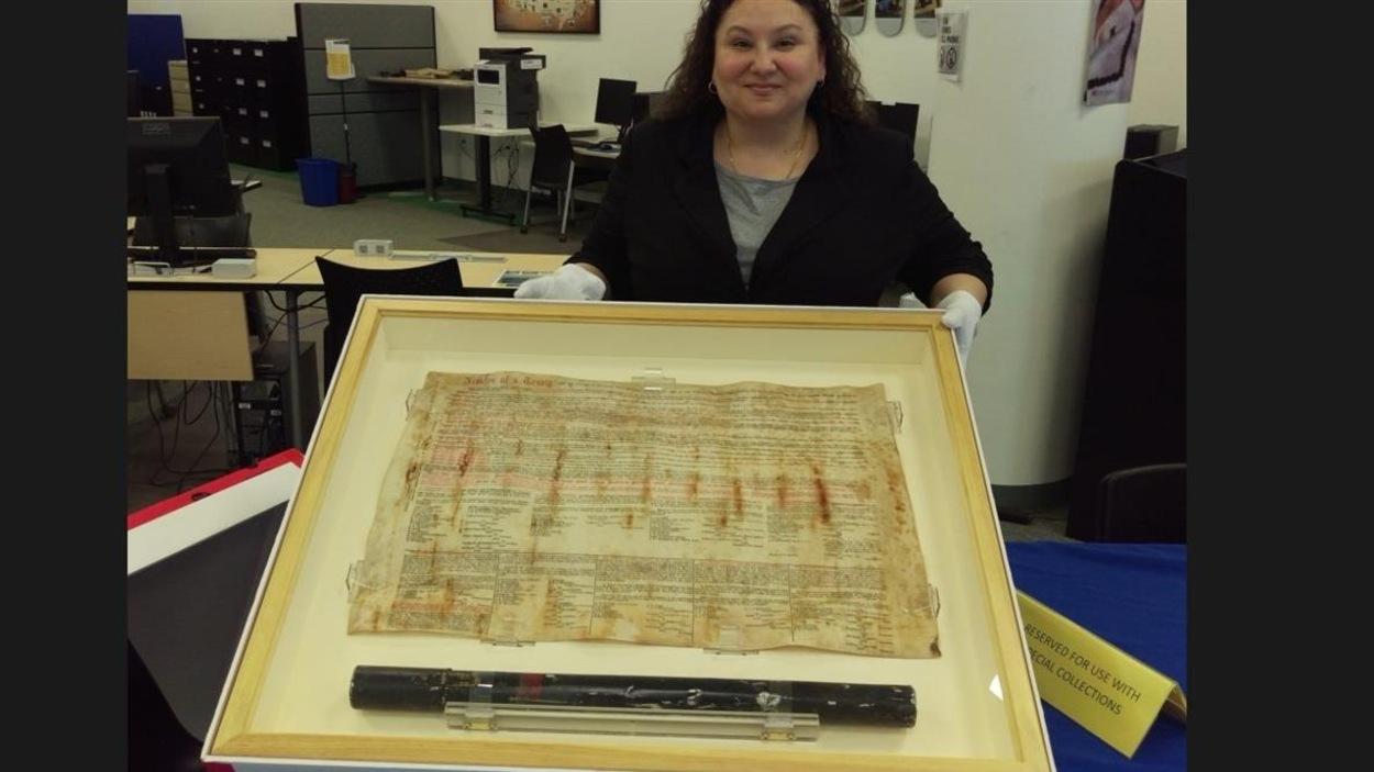 Paula Daigle, bibliothécaire à l'Université des Premières Nations du Canada, montre l'original du Traité 8, datant de 1899.