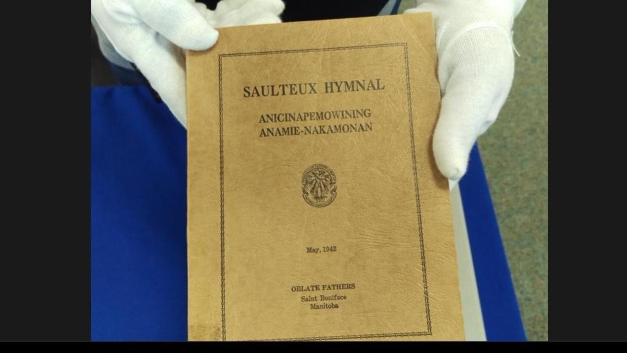 Paula Daigle, bibliothécaire à l'Université des Premières Nations du Canada, montre  la couverture d'un recuil d'hymnes en langue saulteaux.  Il a été imprimé à Saint-Boniface, au Manitoba, en 1942.