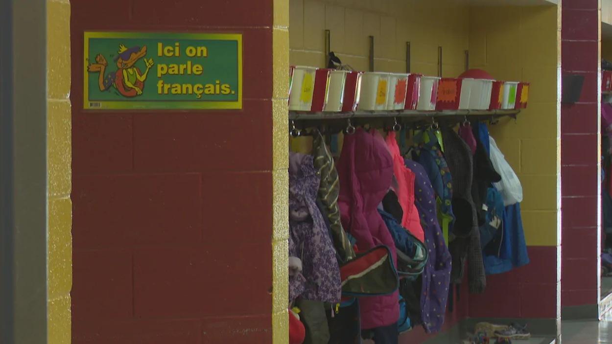 Des manteaux d'élèves dans un vestiaire d'une école. Une affiche indique « Ici, on parle français ».