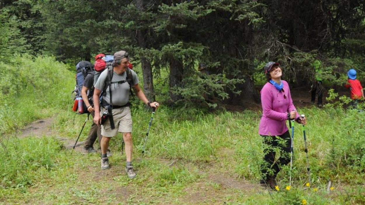 Une jeune femme habillé en rose marche dans les bois. Elle est accompagnée par d'autres participants.