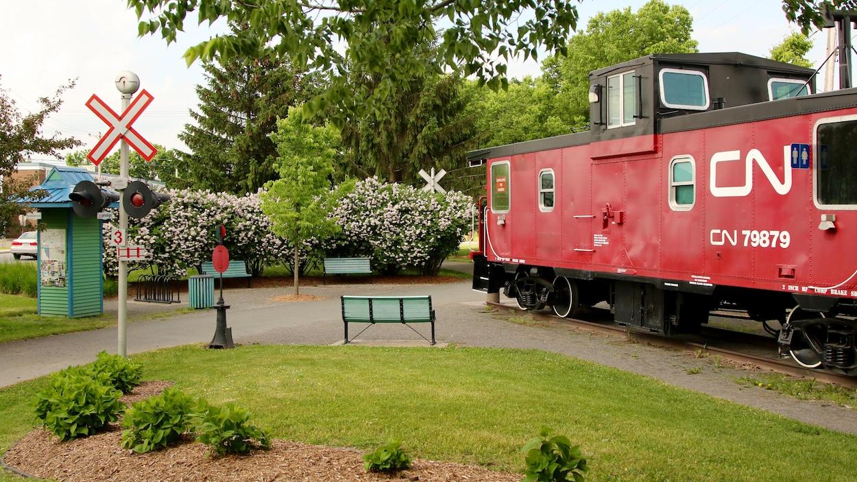 Un wagon de queue rouge du CN dans un jardin fleuri avec des bancs.