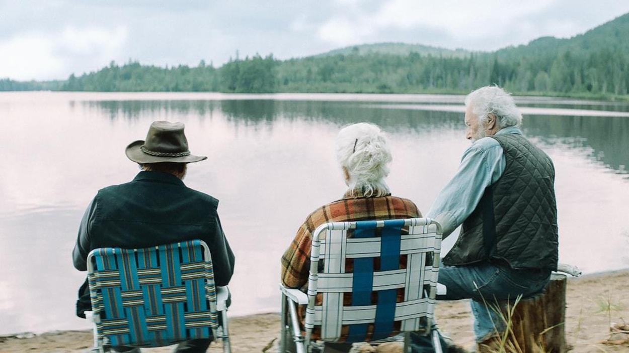 Trois personnes agées font face à un lac.