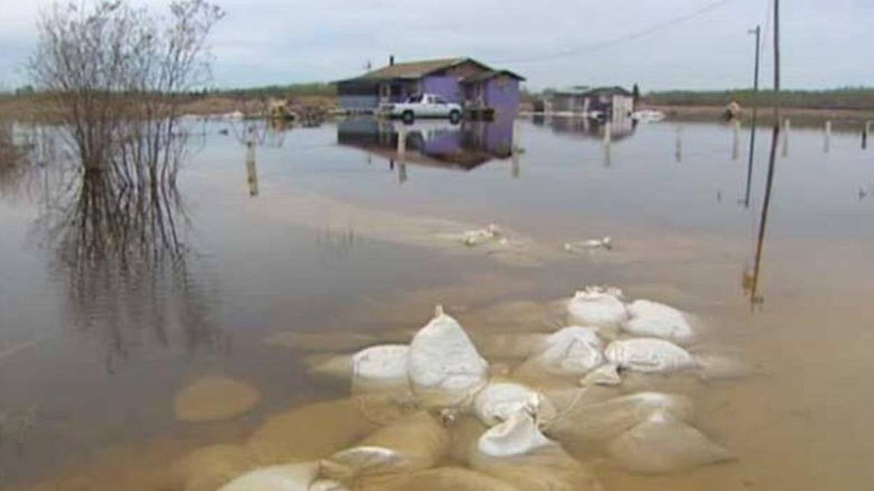 Des sacs de sable devant une maison dans la Première Nation de Little Saskatchewan au Manitoba, touchée par une inondation en 2011.