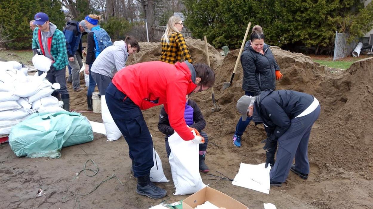 Une dizaine de personnes remplissent des sacs à l'aide de pelles dans un quartier résidentiel.