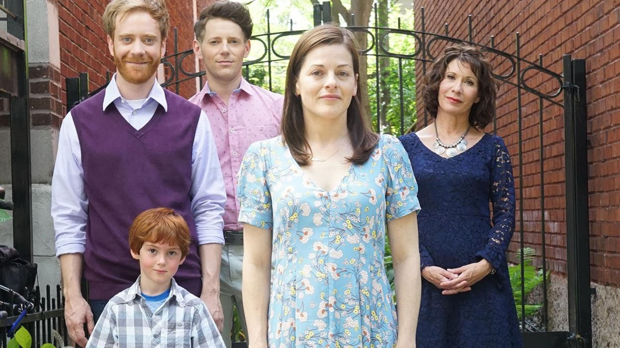 Les cinq personnes, dont un enfant, sont debout et regardent devant eux et elles.
