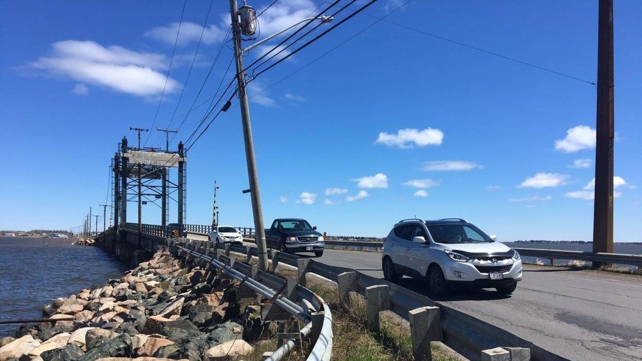 Des voitures sur la route bordée de poteaux électriques neufs