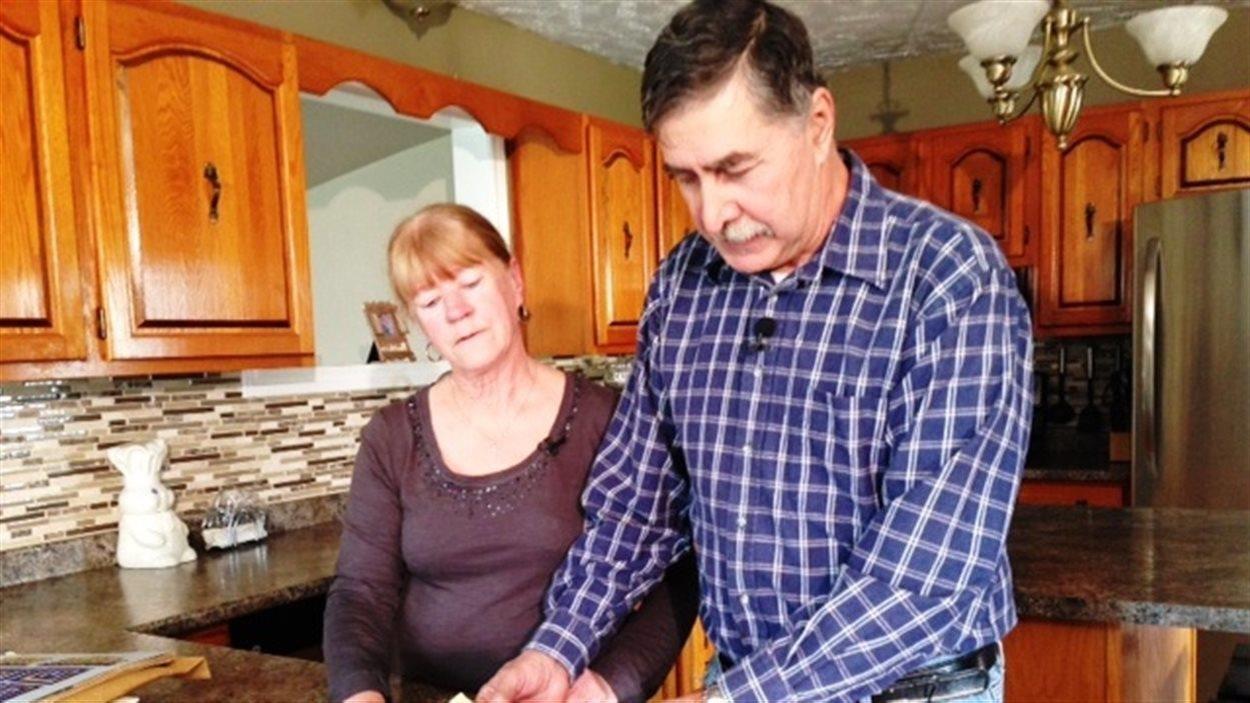 Jacqueline et Oscar LeBlanc consultent des éléments d'enquête dans leur cuisine.