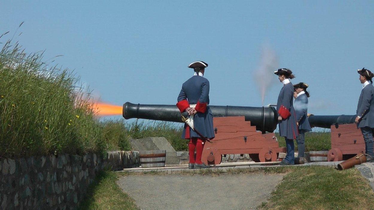 Des figurants en uniforme de soldat font tonner un canon sur un rempart