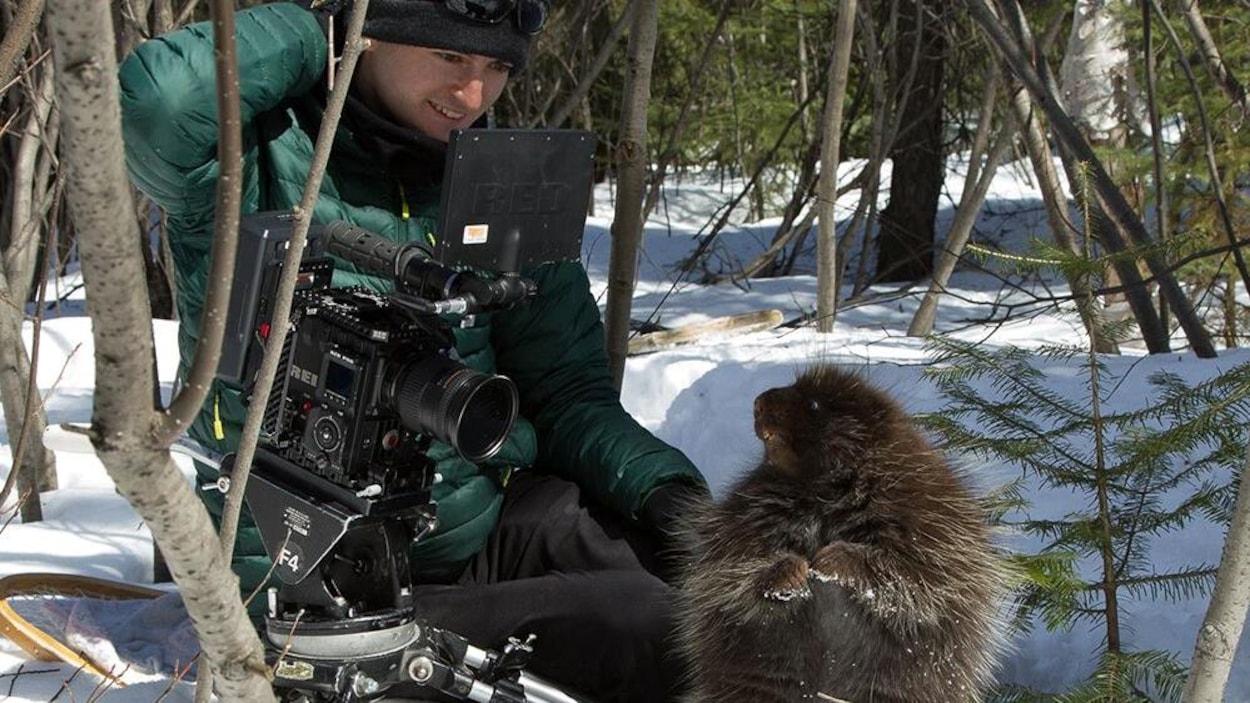 Un homme agenouillé dans la neige, tenant une caméra, pour filmer un porc-épic.