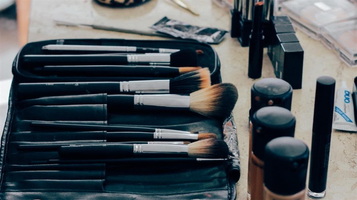 Des produits de beauté : pinceaux à maquillage, rouges à lèvres et fonds de teint.