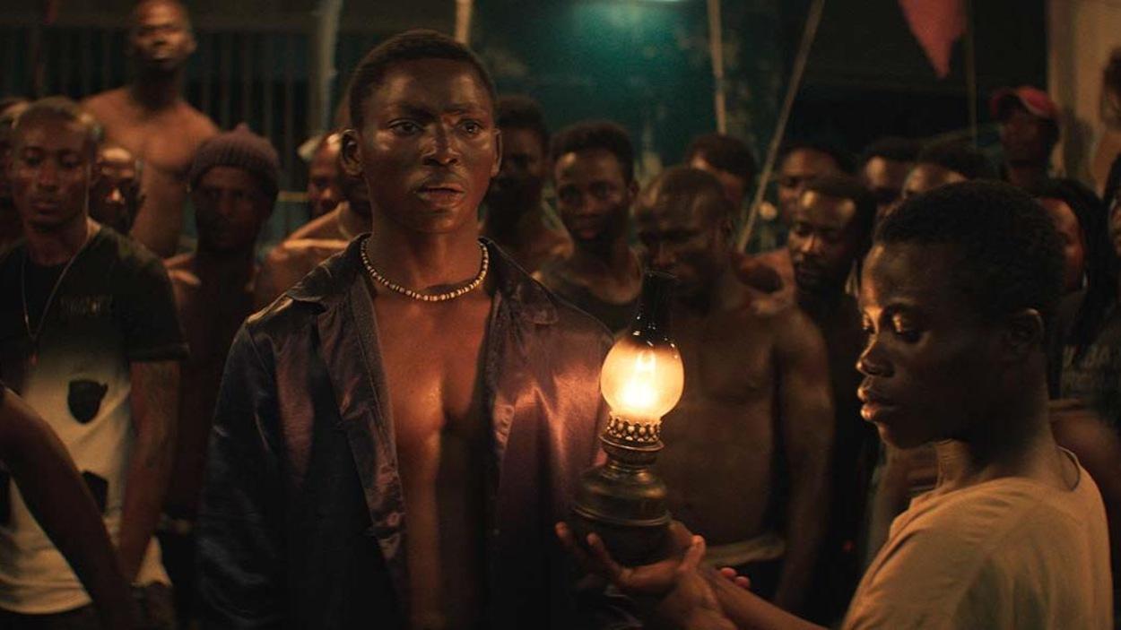 Un homme éclairé par une lampe au milieu d'un groupe.