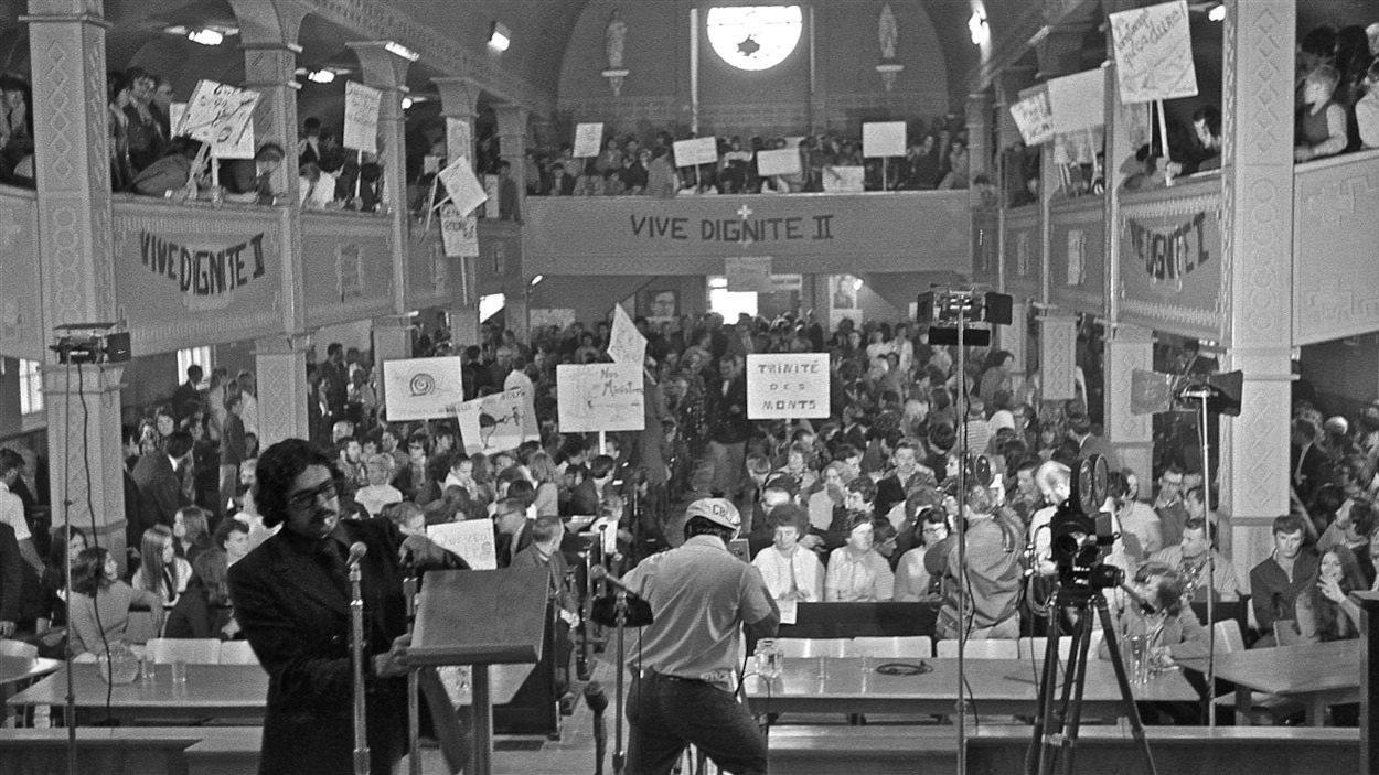 Des personnes sont rassemblées dans une église et tiennent des pancartes.