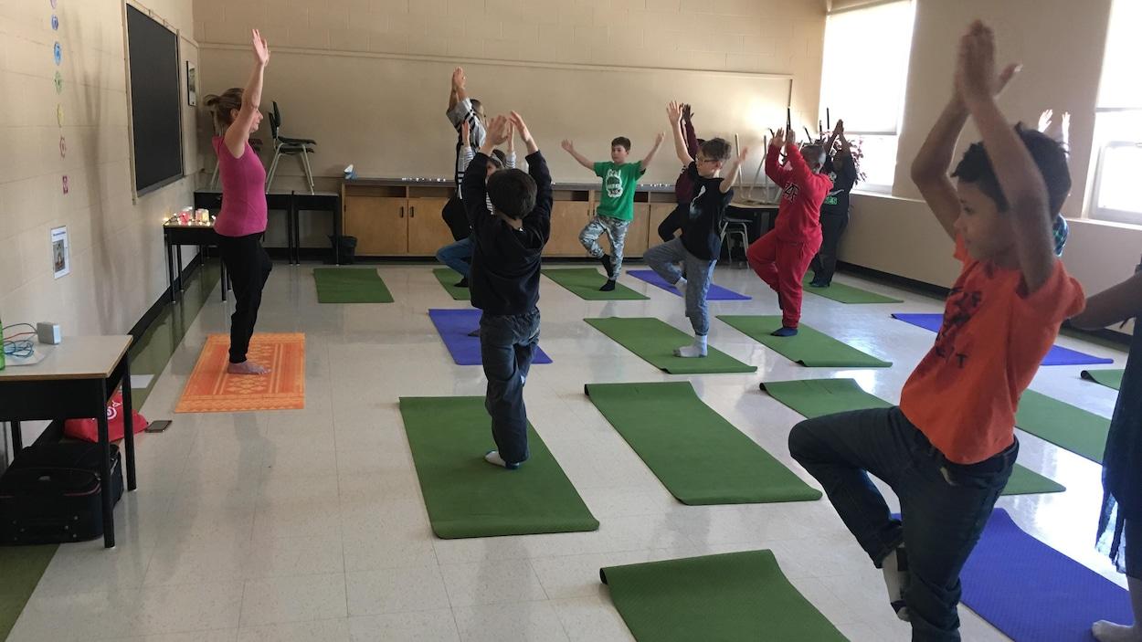 Des élèves se tiennent en équilibre sur des tapis de yoga