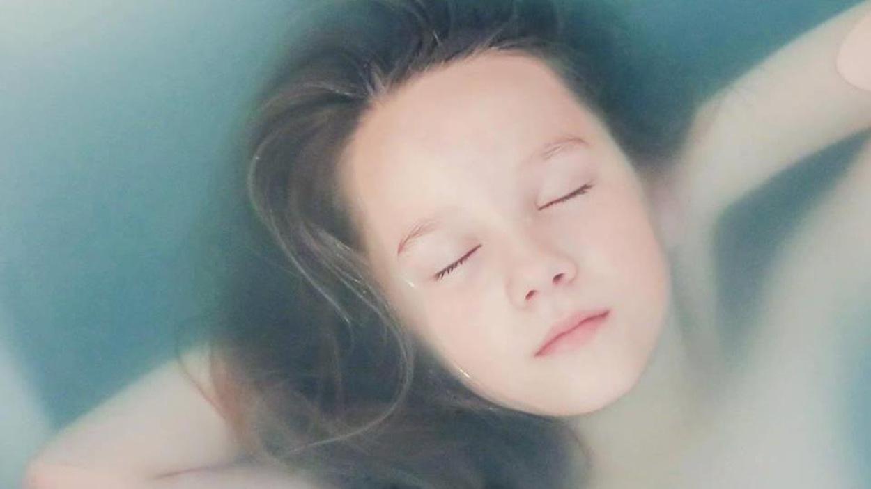 Photographie d'une enfant dans son bain.