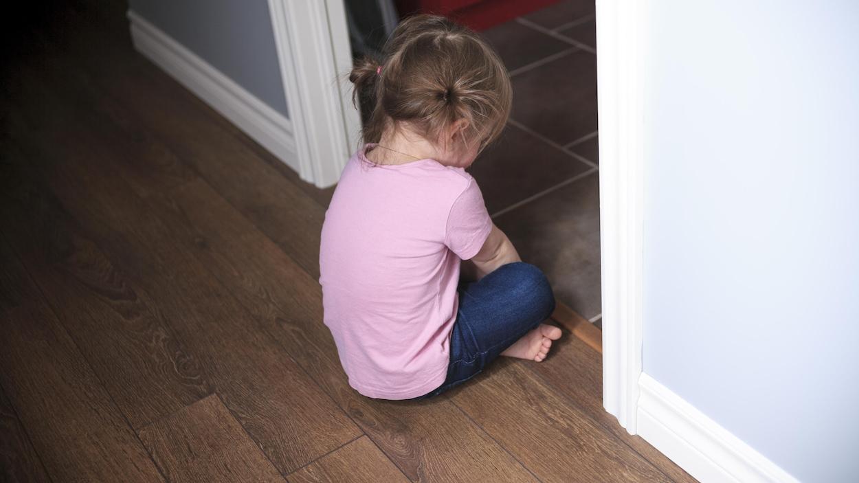 Une fillette assise au sol, l'air fâché, tourne le dos à la caméra.