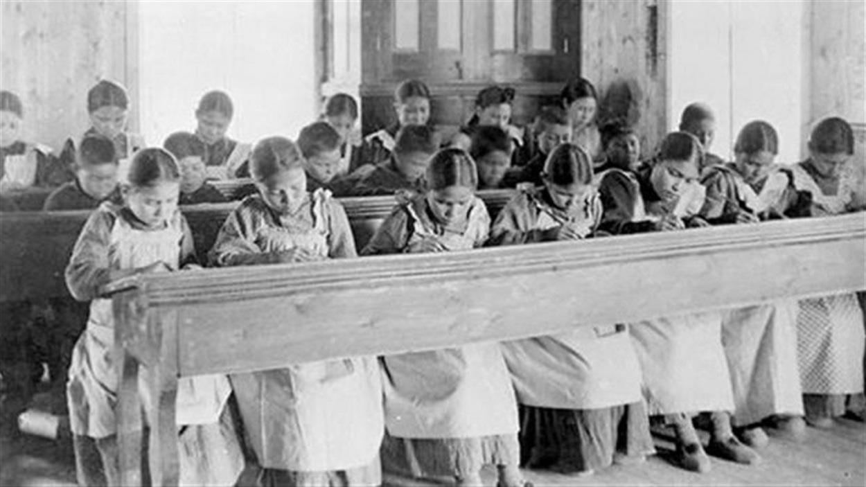 Des jeunes autochtones sont assises et font leur devoir dans un pensionnat autochtone.