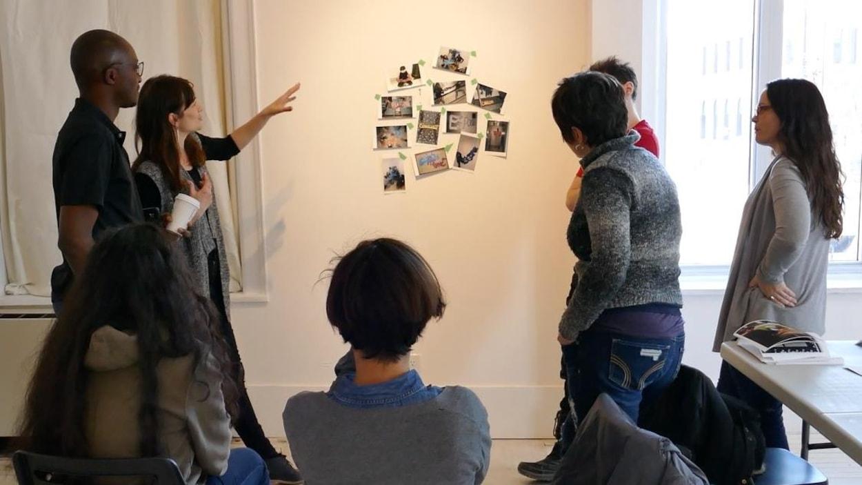 L'artiste Dominique Rey pointe et parle aux participants au sujet des photos accrochées au mur.