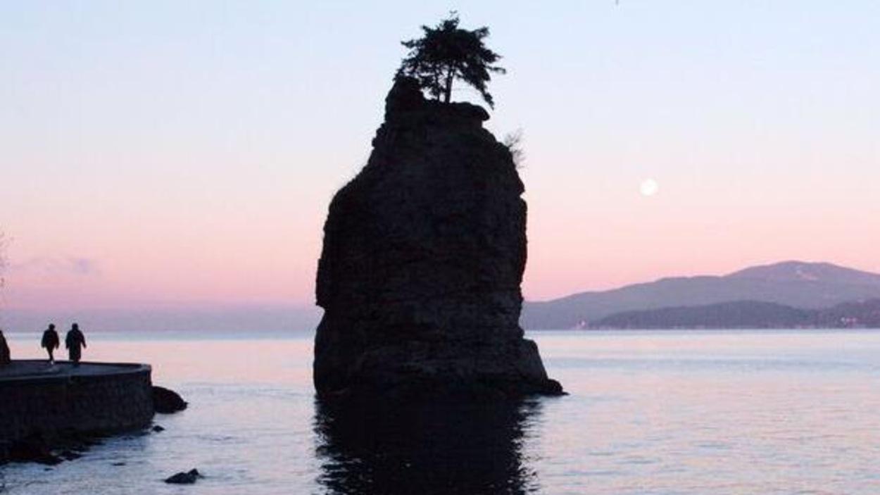Un rocher debout dans l'eau près d'une promenade où il y a deux marcheurs avec montagnes en toile de fond