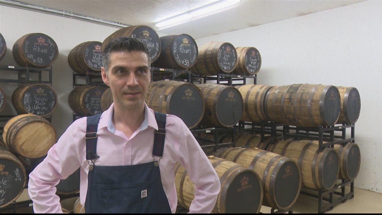 Photo du propriétaire de la distillerie Fils du Roy, Sébastien Roy, devant des barils de rhum et de whisky.