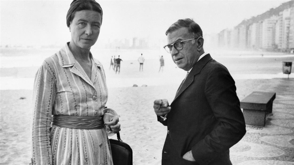 Simone de Beauvoir et Jean-Paul Sartre regardent l'objectif en se retournant alors qu'il sont sur la plage de Copacabana, à Rio, en 1960.