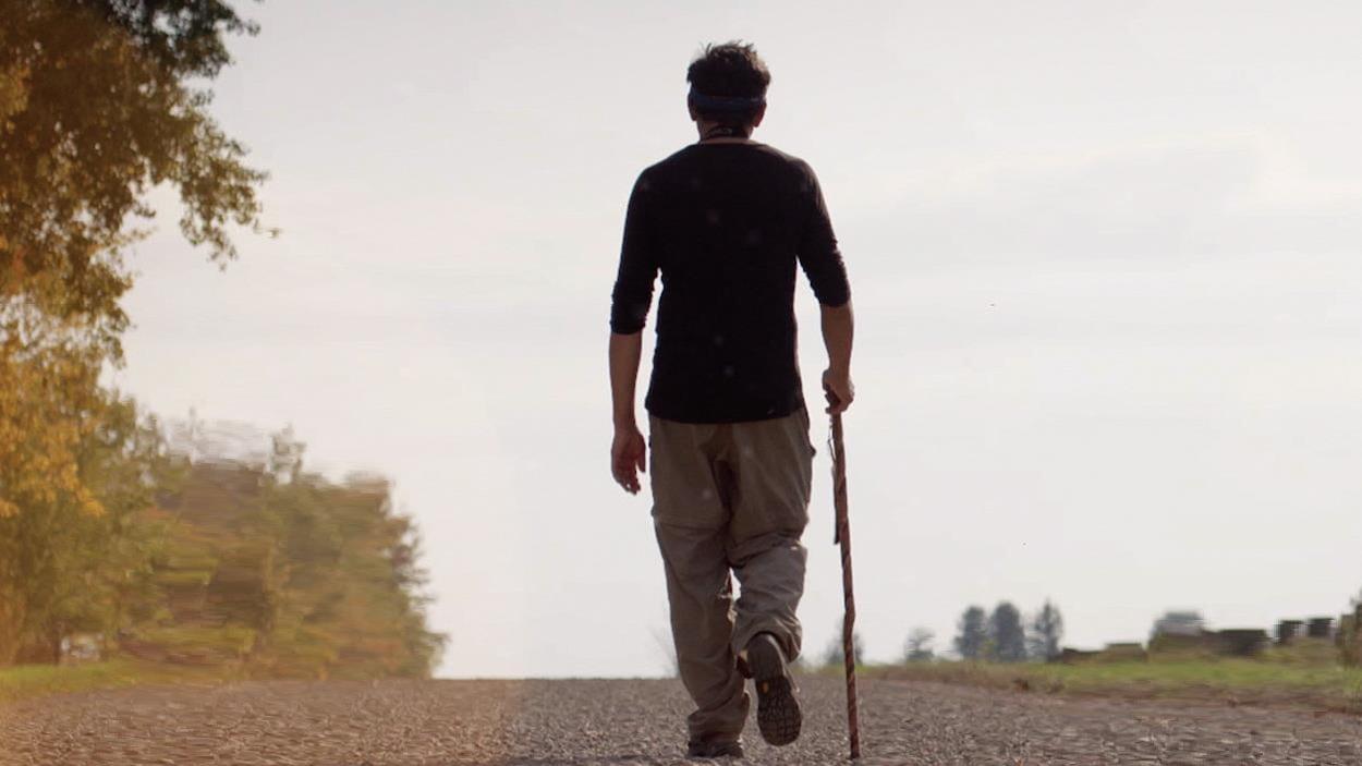 Stanley Vollant s'éloigne en marchant seul sur une route