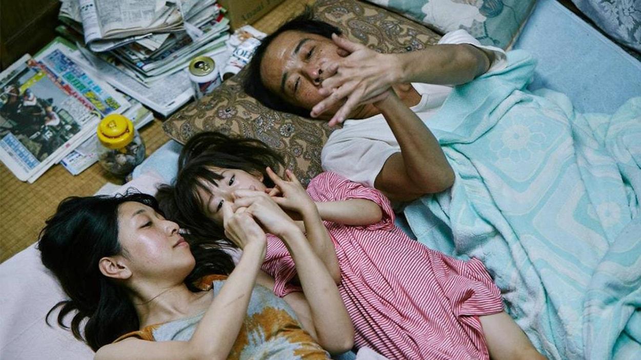 Deux adultes, une femme et un homme, entourent une enfant et comptent sur leurs doigts.