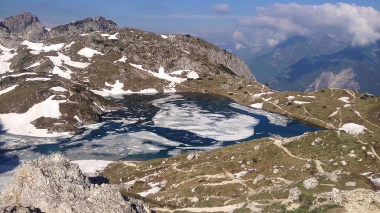 Un lac alpin à demi-glacé dans les Dolomites