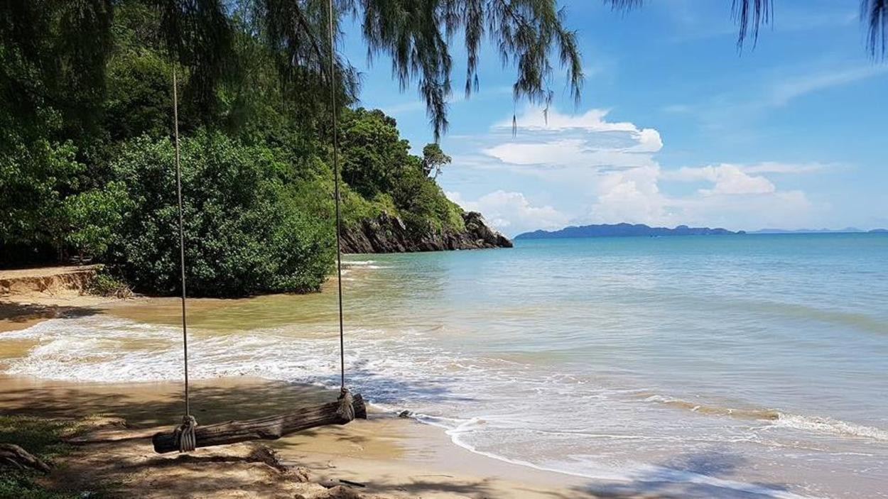 Une balançoire, la mer et des arbres du parc national de Mu Koh Lanta, en Thaïlande