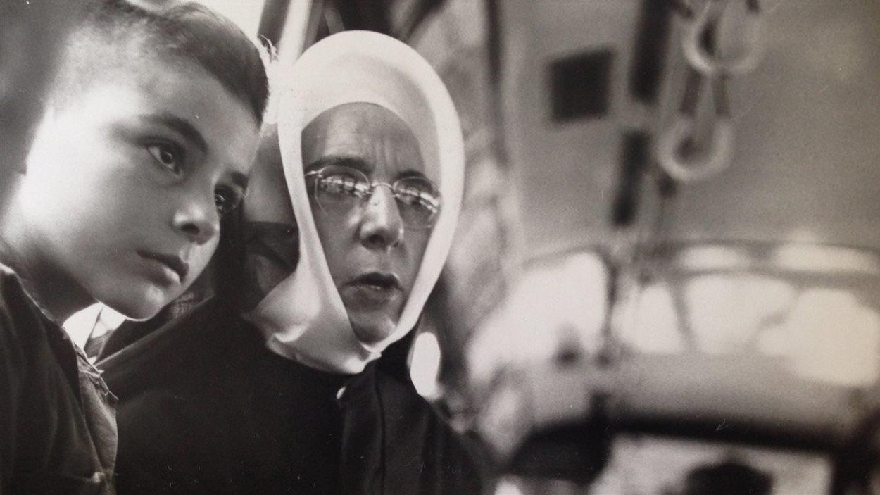Une religieuse accompagnant un jeune garçon dans un autobus, à Montréal, été 1950.