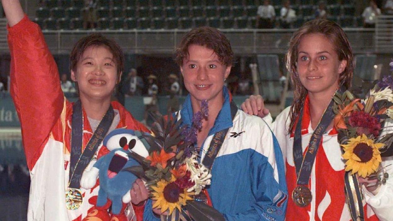 Trois femmes en survêtement avec une médaille au cou posent pour les photographes devant une piscine olympique.