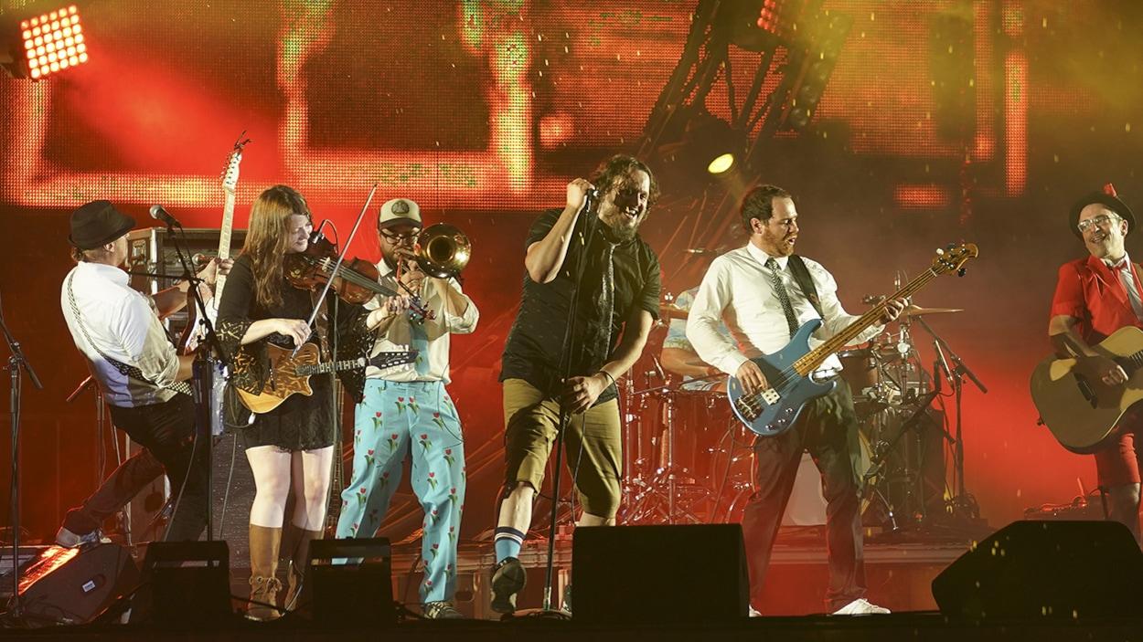 Les Cowboys Fringants sur une scène en train de chanter et jouer des instruments.