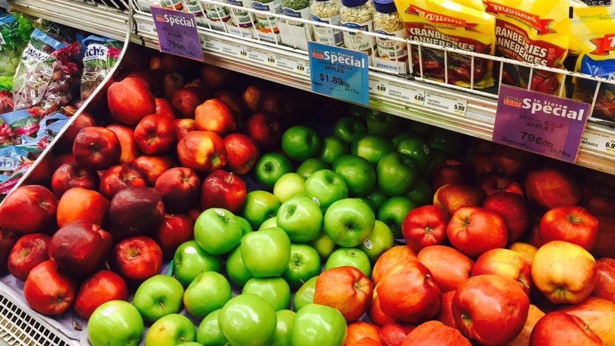Des pommes affichées en solde dans un présentoir.
