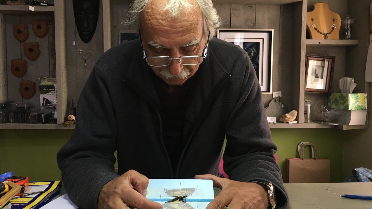 Guy Leblanc pose en train d'épingler un papillon