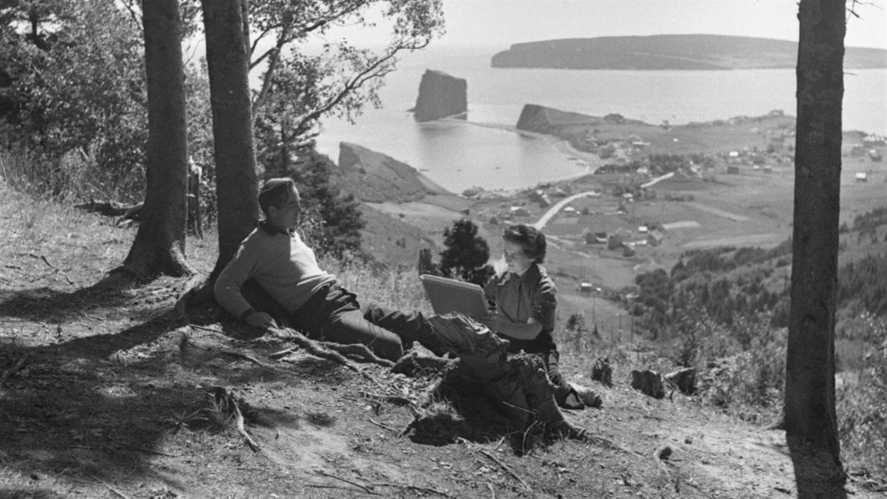L'artiste Suzanne Guité réalisant un portrait de son mari, Alberto Tommi, au Pic de l'Aurore, à Percé, 1950.