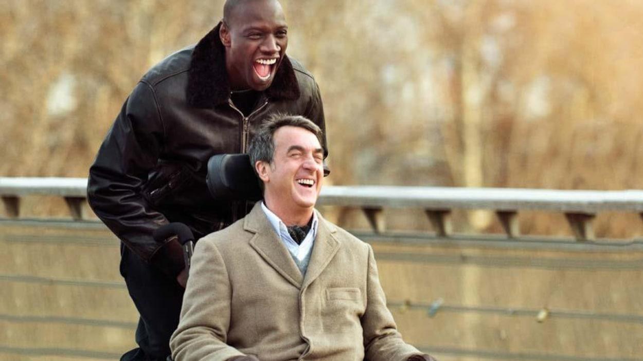 Un homme pousse un autre homme qui est en chaise roulante. Les deux rient.
