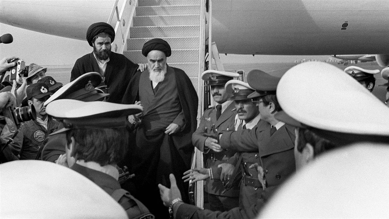 Un homme dans un costume religieux descend d'un avion devant un attroupement de soldats et de journalistes; tout juste derrière lui et de côté, un homme a une main sur son épaule.