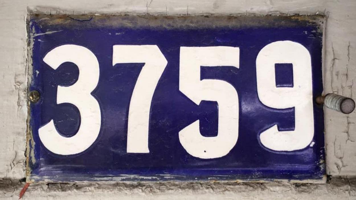 Un plaque de métal bleue avec des chiffres blancs dessus.