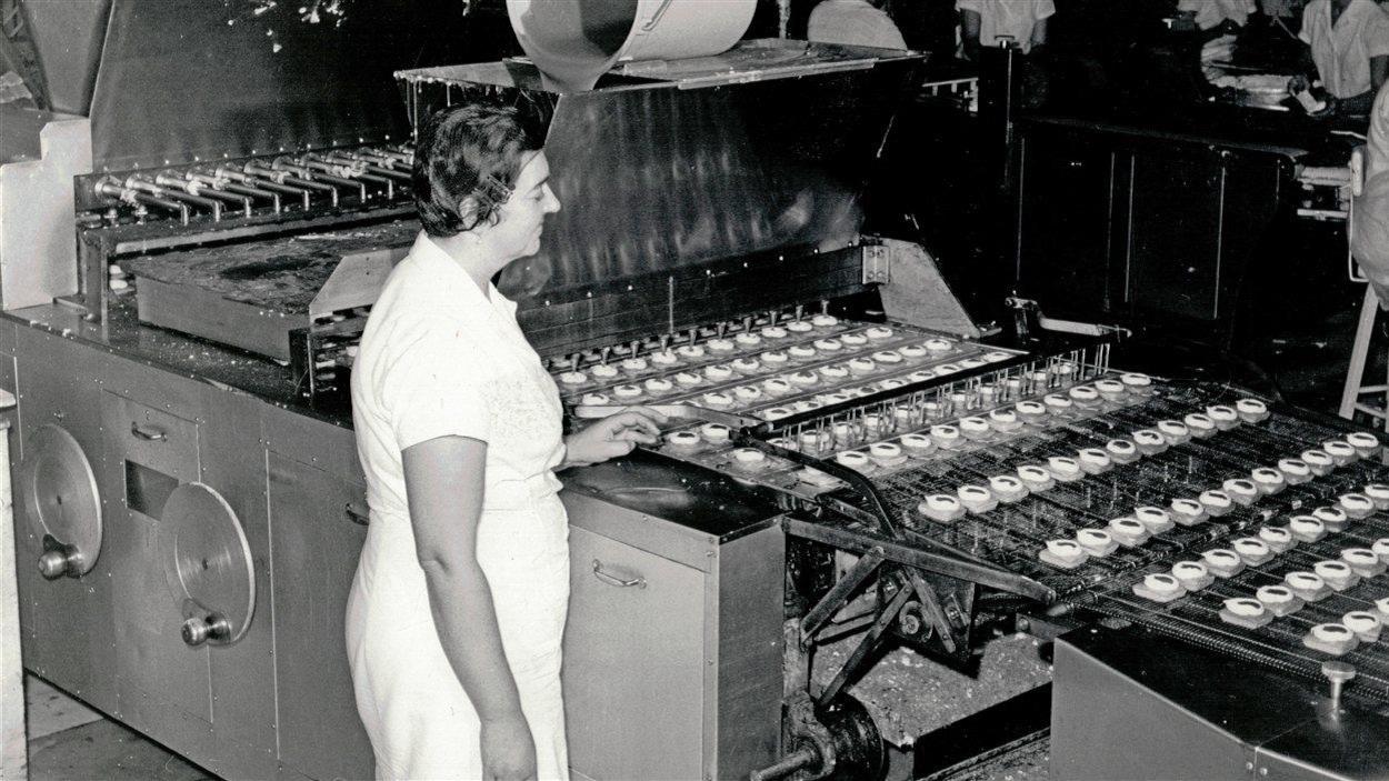 Une employée surveille la production des gâteaux au caramel à l'usine de petits gâteaux Vachon dans les années 60.