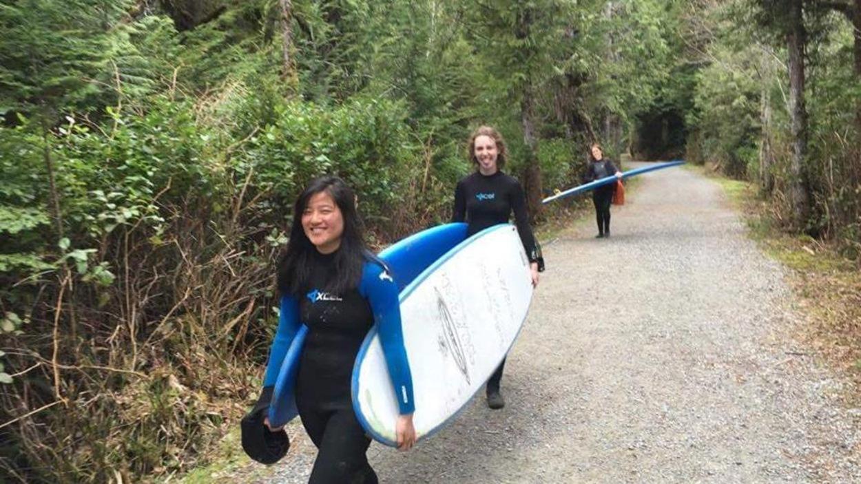 Sabrina Gagnon est ses amies transportent des planches de surf dans un sentier.