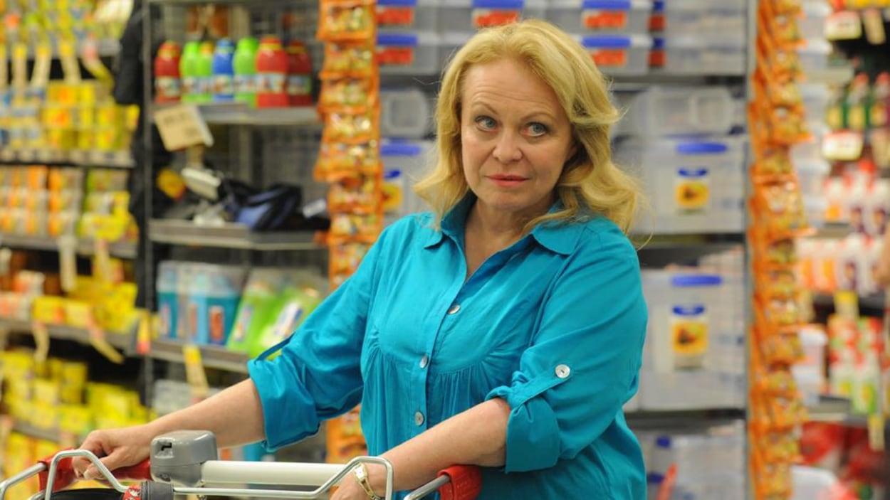 Une femme en blouse bleue pousse son chariot au supermarché
