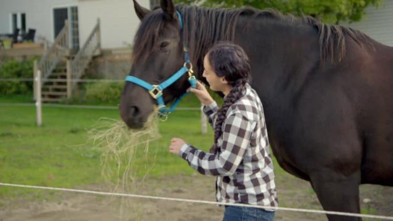 Une femme promène un cheval