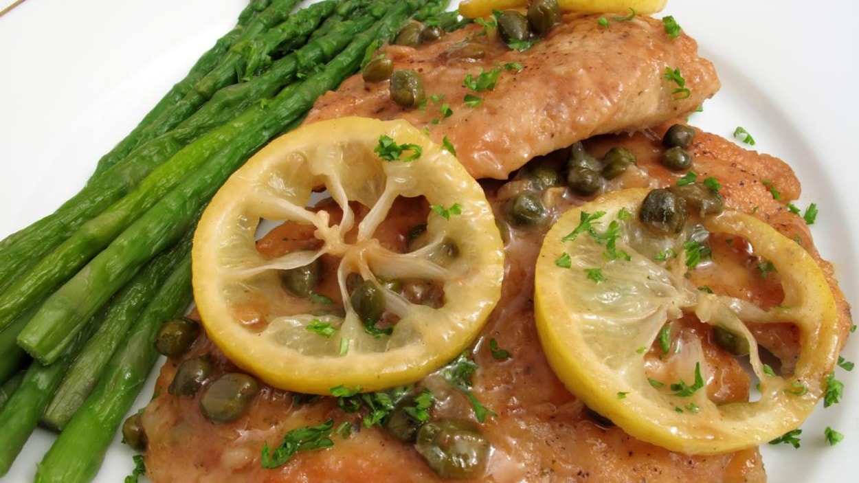 Photo of Italian recipe called chicken piccata.  This is chicken scaloppine or chicken breast cutlets cooked with a sauce made of capers, white wine, lemon slices and butter.  Parsley is sprinkled on top.  Asparagus is served with the chicken as the vegetable.
