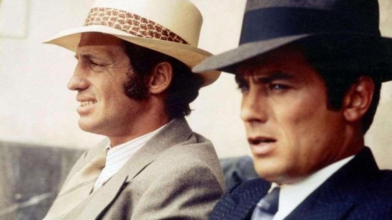 Deux hommes (Jean-Paul Belmondo et Alain Delon) de profil, portant costumes et chapeaux.