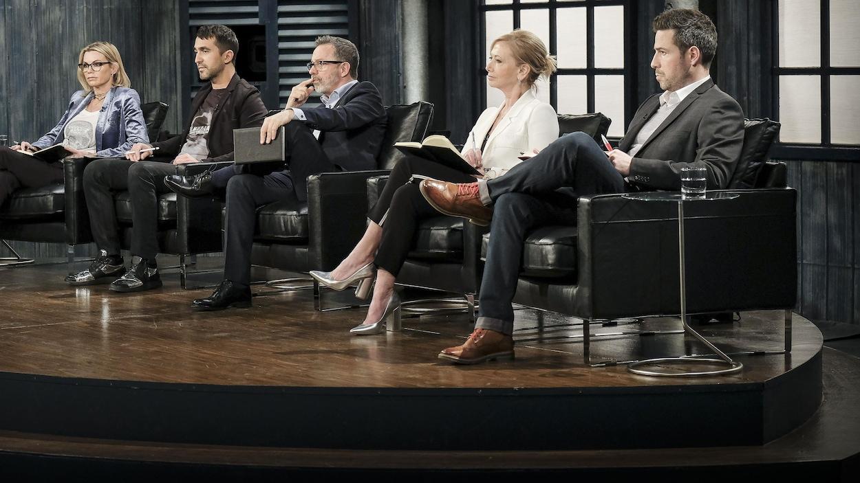 Ils regardent très attentivement la présentation d'un entrepreneur. Ils sont assis dans des fauteuils en cuir noir.